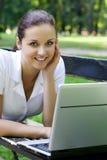 Woman using laptop on bench outdoors Stock Photos
