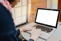 Woman using laptop with blank screen on table Royalty Free Stock Image