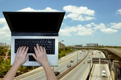 Woman using laptop with blurry expressway background stock image