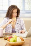 Woman using laptop at breakfast Royalty Free Stock Photo