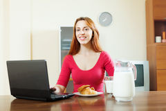 Woman using laptop during breakfast Stock Photos