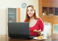 Woman using laptop during breakfast Royalty Free Stock Photos