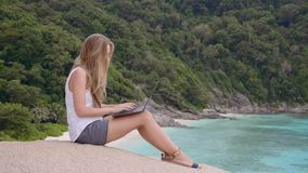 Woman using laptop. Business woman using laptop computer on top of the mountain with a view over white sand beach. Vacation, freelance job, leisure activity stock video