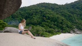 Woman using laptop. Business woman using laptop computer on top of the mountain with a view over white sand beach. Vacation, freelance job, leisure activity stock footage