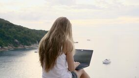 Woman Using Laptop. Business woman using laptop computer on top of the mountain with a view over white sand beach. Vacation, freelance job, leisure activity stock video footage
