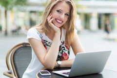 Woman using laptop at cafe Stock Photo