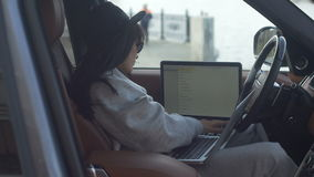 Woman using laptop in car. Side view of trendy female sitting in car and using laptop stock video