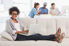 Woman using laptop with colleagues in background at creative office Royalty Free Stock Images