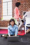 Woman using laptop with colleagues behind in office Stock Image