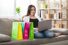 Woman Using Laptop With Colorful Shopping Bags Royalty Free Stock Photo