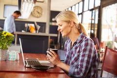 Woman using laptop computer at a coffee shop Stock Photos