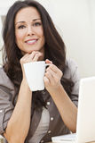Woman Using Laptop Computer Drinking Tea or Coffee. Beautiful, smiling, young brunette woman at home at a table using her laptop computer and drinking a mug of stock photography