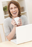 Woman Using Laptop Computer Drinking Tea Coffee stock photo