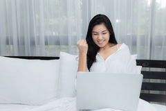 Woman using a laptop computer on her bed Stock Images