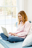 Woman using laptop computer at home Stock Image