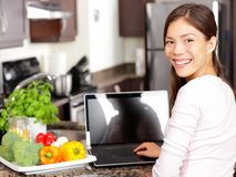 Woman using laptop computer in kitchen. With greens and vegetables. Lifestyle cooking concept with smiling happy mixed-race Asian chinese Caucasian woman Royalty Free Stock Photography