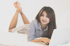 Woman using a laptop computer while lying on her bed Stock Photography