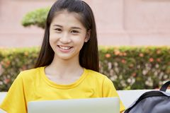 Woman using a laptop computer in a park. Young asian woman using a laptop computer in a park stock photos