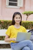 Woman using a laptop computer in a park. Young asian woman using a laptop computer in a park stock photo