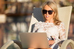 Woman using laptop computer while sitting in deck chair Stock Images