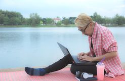 A woman using laptop computer while sitting beside river royalty free stock image