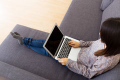 Woman using laptop computer. On sofa Royalty Free Stock Images