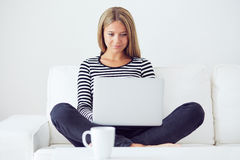 Woman using laptop computer on sofa royalty free stock photography
