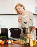 Woman using laptop while cooking Royalty Free Stock Photos
