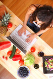 Woman using a Laptop while cooking Royalty Free Stock Photos