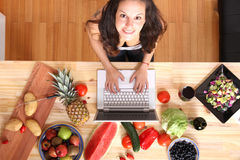 Woman using a Laptop while cooking Stock Photos