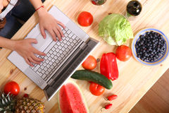 Woman using a Laptop while cooking Stock Photo