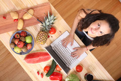 Woman using a Laptop while cooking Stock Photography