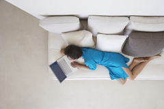Woman Using Laptop On Couch In Living Room Stock Photos