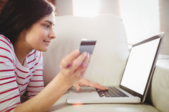 Woman using laptop on couch Royalty Free Stock Images