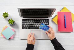 Woman using laptop and credit card for online shopping. On wooden background Royalty Free Stock Images