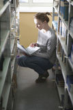 Woman Using Laptop While Crouching At Bookshelves Stock Photo
