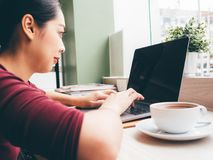 Woman is using laptop with a cup of hot coffee in the cafe. Asian woman is using laptop with a cup of hot coffee in the cafe stock photography