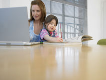 Woman Using Laptop While Daughter Coloring Book At Table Stock Photography