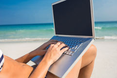 Woman using laptop on deck chair Stock Photo