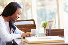 Woman Using Laptop On Desk At Home royalty free stock photos