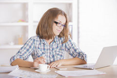 Woman using laptop and doing paperwork Stock Image