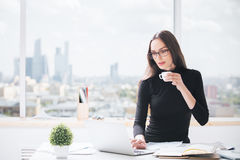 Woman using laptop, drinking coffee Stock Photography