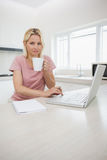 Woman using laptop while drinking coffee in kitchen Stock Photo