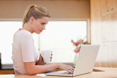 Woman using a laptop while drinking a cup of a tea Stock Photo