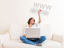 Woman using laptop and drinking from a mug Royalty Free Stock Photo