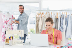 Woman using laptop with fashion designer working at studio Royalty Free Stock Image