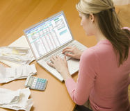 Woman Using Laptop for Finances. High angle view of a young woman using a laptop computer to organize her finances.  Horizontal shot Royalty Free Stock Images