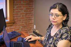 Woman Using Laptop And Focuses On Task At Hand Royalty Free Stock Photos