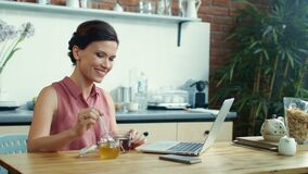 Free Woman Using Laptop For Video Call Online. Girl Pouring Honey Into Cup Of Tea. Stock Images - 193114984