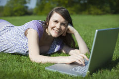 Woman Using Laptop On Grass Stock Image